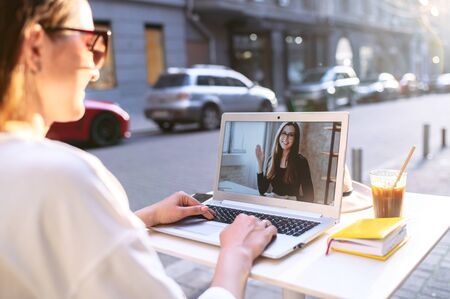 Virtual meeting with a friend. Young woman sits at the table in the street cafe and uses laptop for video call to another woman, two female friends are talking online Foto de archivo
