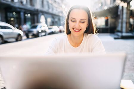 Young attractive woman sits at the table of outdoor cafe on a cozy european street with a laptop in warm natural sunlight. Close-up shot Reklamní fotografie