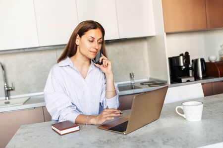 Responsible woman answers phone calls, takes online orders from store intranet working remotely from home. Distance work concept 스톡 콘텐츠