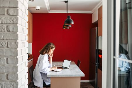 Work on the distance. Young woman uses laptop for working from home, she sits at the kitchen table in loft style interior and talking on the smartphone 스톡 콘텐츠