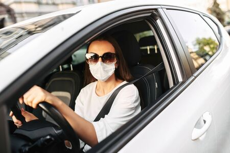 Young woman in sunglasses with protective medical mask driving a car, she holds hands on the steering wheel and looking into camera. Safety during coronavirus pandemic, epidemic covid-19