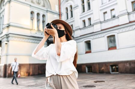 Tourism after quarantine. Young girl tourist in a protective medical mask walks around the city and photographs the sights