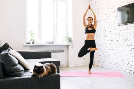 Yoga time for a young fit girl. Her hands up in the air pointed directly upwards clasped together, while her leg is bent in knee. Cosy living room with a cat on a couch on the background