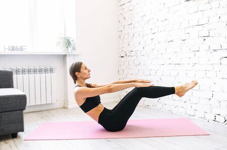 Young sporty woman trains at home, she is doing her abs workout, her arms and legs are stretched in front of her, healthy fit body