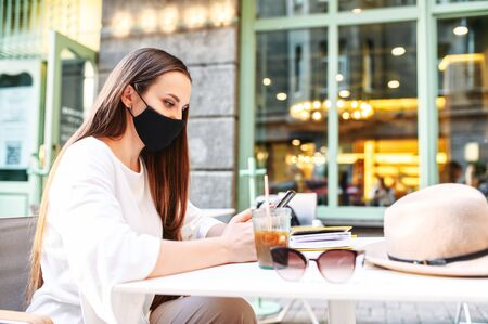 A young woman with a medical mask on the face is resting in a summer cafe. The girl sits at a table on the summer terrace and uses the phone, she protects herself with a mask from virus, allergy Archivio Fotografico