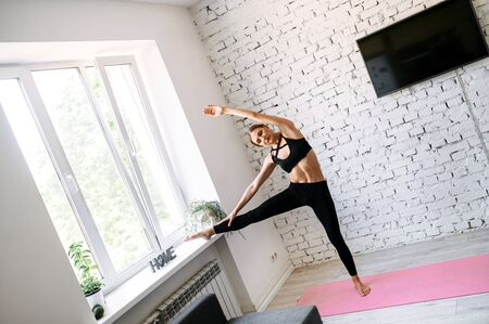 Stretching of a girl at home. She stands near the window with one leg on a windowsill while reaching with her hand to her foot. Home workout, healthy lifestyle