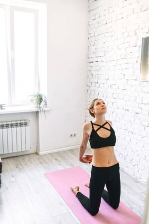 Young woman warms up before a home workout. She stands on her knees with her hands locked together behind her back, looking up