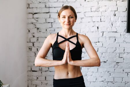 Young woman is practicing yoga at home. A midshot of a young girl with her hands clasped together in front of her chest in namaste, she has a calm and peaceful look on her face