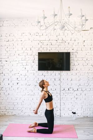 Vertical side shot of a fit woman stretching before a home workout. She stands on her knees with her hands locked together behind her back, looking up. White brick wall with a TV on it on the background