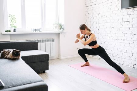 Sporty girl is doing morning exercises. She leans on a one leg while stretching the other, her hands are put together in front of her. Cosy living room with a cat on a couch ob the background