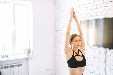 Young woman is practicing yoga at home. A mindset of a young fit girl doing yoga at home, her hands are put up together in the air. Foto de archivo