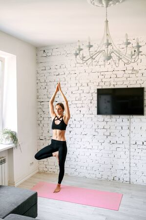 Calm young woman practicing yoga at home. Hands are held above the head and pointed directly upwards, right knee is bent and the right foot placed on the left inner thigh. Vertical shot