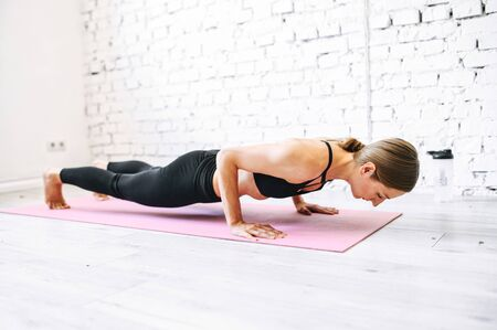 Sporty woman in plank while home workout. She leaned low over the floor in her arms bent in elbows, looks like she is doing push-ups. Keeping herself fit