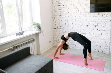 Young fit girl stands in a bridge while a home workout. She is doing her exercises at home on a fitness mat, stretching, healthy habbits
