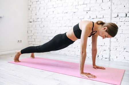 Young woman stands in plank while home workout. She is standing on outstretched arms on a mat looking on the floor.