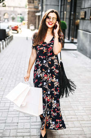 Vertical shot of attractive brunette girl in long summer dress outdoors, girl wearing sunglasses with a shopping bags is walking among stores in the city and talking on the phone