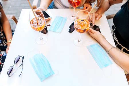 Meeting with friends in the cafe after quarantine ended. Top view three medical masks on the table, cocktails are near on the table and female hands in the summer terrace. Relief of quarantine 版權商用圖片