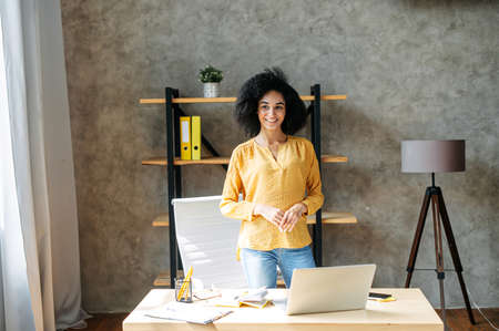 Cheerful young an ethnic woman with an afro hairstyle stands in contemporary office, looks away and smiled mysteriously