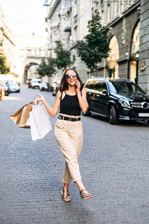 Carefree beautiful young woman in long summer dress walks outdoors and talks on the phone after shopping day, paper bags with purchases in her hand. Full length