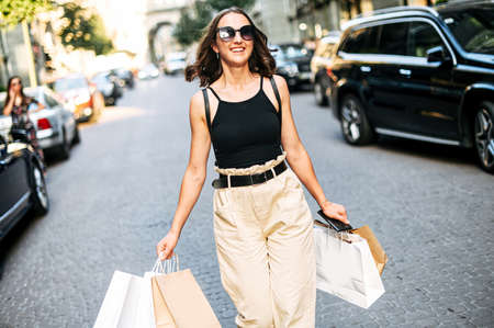 Shopping day. Happy young stylish girl in sunglasses walking on the street with a paper shopping bags in her hands