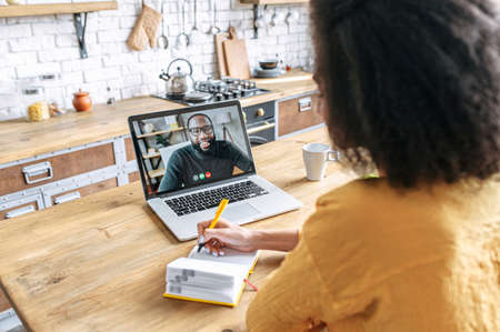 A female student studies online. An african woman is watching online classes and writing a syllabus in notebook, black male tutor on the screen. Concept of distance study, online learning, webinars
