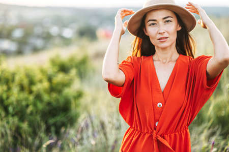 Charming girl in hat posing in the countryside. Woman in red looks at camera with a passion