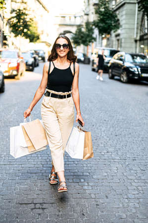 Charming young woman has a shopping day in the city, she walks on the street with shopping bags in her hands and looks around with a smile