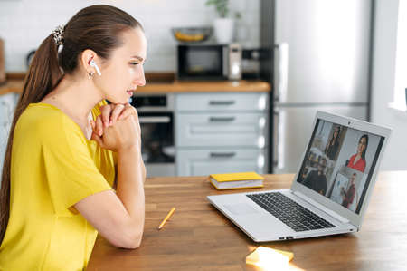 A girl is using app for distance video communication with coworkers, friends. People profiles of multiracial team on a laptop desktop. Online meeting, webinars