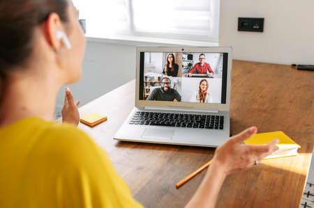 Virtual conference, online meeting. Young woman uses laptop app for communicating with several people friends or employees at same time together. Back view. Video call concept Banque d'images