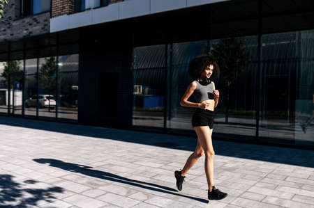 Healthy and athletic African woman running on the city street. A biracial girl is jogging in the morning. Full length 스톡 콘텐츠