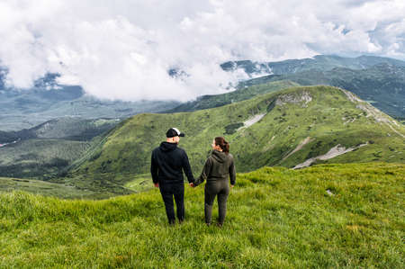 Back view of a guy and a girl hikers stand and holding hands with a spectacular view. Couple in love hike in a mountains Banco de Imagens