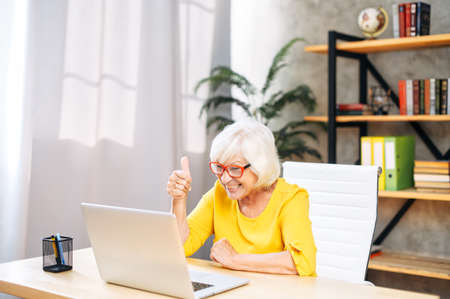 Mature woman is using a laptop computer for online video call at home office. A cheerful gray-haired lady is giving thumb up at webcam
