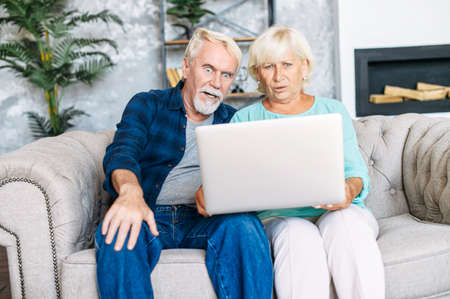 Elderly spouses are sitting at home on the couch with a laptop and stared at screen with big eyes in disbelief. Unbelievable news got senior couple excited