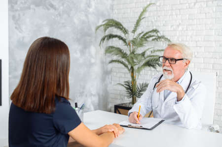 Senior male doctor looks on patient with an empathy and care. Doctor visit concept