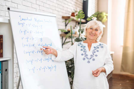 A senior woman in smart casual shirt is writing on flipchart and smiles. Online teacher, tutor. Side view
