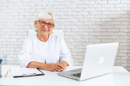 Mature gray haired female doctor is using laptop in hospital office. Senior woman in white formal coat on the white background