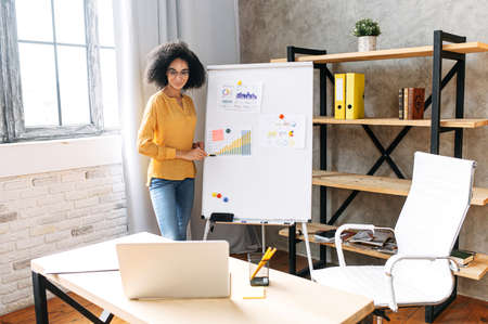 Intelligent african american woman in eyeglasses conducts online webinar, business training, girl stands near whiteboard and talks to online audience on the laptop screen