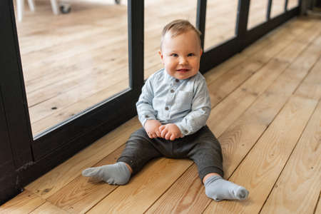 A cute little child sits on the wooden floor indoor. A baby boy looks at camera and smiles
