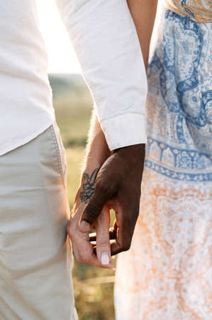 Close up picture of black male hand holds white tattooed female hand. Romantic date