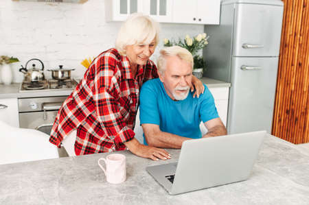 Elderly spouses in embrace using laptop in the kitchen at home Standard-Bild