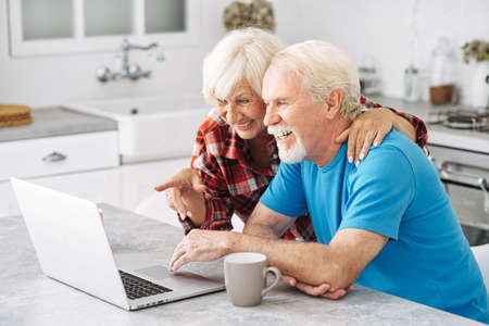 Cheerful senior couple looks with interes on laptop screen. Grey-haired smiled spouses make shopping together Standard-Bild