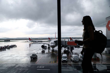 Travels concept. A silhouette of young woman in airport with a huge airplane and cloudy sky on a background. A girl with a backpack is waiting for boarding
