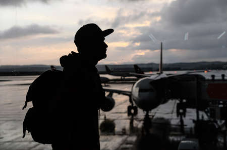 Travels concept. A silhouette of young man in airport with a huge airplane on a background. A guy with a backpack is waiting for boarding