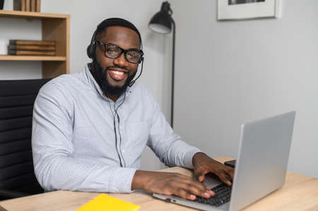 Smiling young African-American employee working on a laptop, using the headphones and microphone for the online conference. A successful businessman sitting in the office at the modern desk