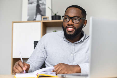 The young and handsome African-American businessman in glasses sitting at the desk and making notes while on video-call with the client, attentively listening and writing down, looking in the window
