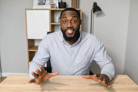 Well-educated and intelligent young African American therapist is asking to take a deep breath and calm down, sitting at the desk, looking at the camera, raising hands up, personal development concept