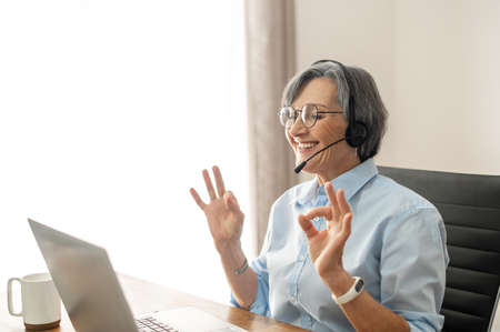 Senior lady call center operator with a grey hair sitting at the desk, wearing glasses and a headset, looking at the screen, mature female office worker showing okay sign approval to the client
