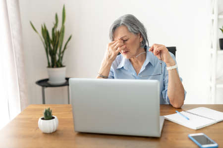 Tired and overworked stressed mature woman working on laptop at home indoor, female teacher feeling exhausted after lecturing students online, touching eyes. Smart working senior people and technology