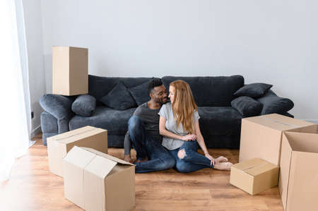 Cheerful young multiracial couple in love moves to new house, diverse couple sits on the floor among the cardboard boxes, looking to each other with smile and love. Multi-ethnic spouses got a mortgage