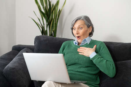 A surprised senior mature woman received exciting and positive news and cannot believe her eyes, looking at the laptop screen and placed her hand on a chest, lucky grandmother won a lottery